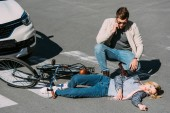 Photo young man near injured woman calling ambulance after car accident on road