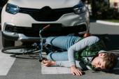 Fotografie zraněný cyklista ležel s kolo na silnici po kolize motorových vozidel