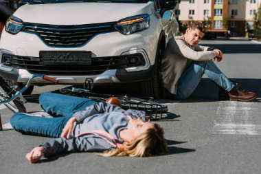 selective focus of injured woman lying on road after car accident with car driver behind