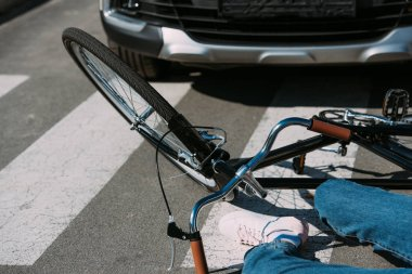 partial view of woman with bicycle mowed down by car on road, car accident concept