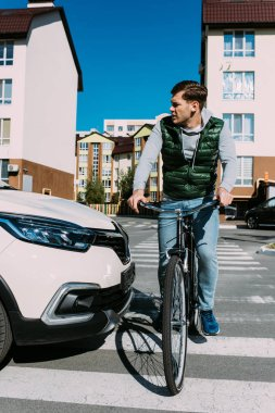man on bicycle crossing road while driver in car waiting
