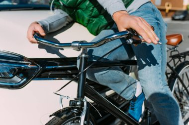 partial view of male bicycle rider hit by car on road, car accident concept