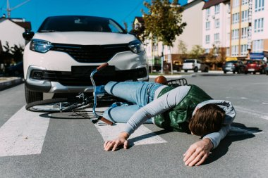 male bicycle rider hit by car on road, car accident concept