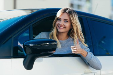 portrait of blond smiling woman showing thumb up while driving car