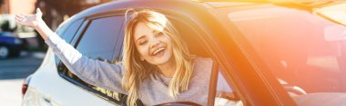 Portrait of happy blond woman waving to someone while driving car stock vector