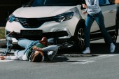 Fotografie cropped shot of woman running to injured cyclist at traffic accident