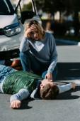 šokovaná mladá žena při pohledu na zraněn mladý cyklista ležící na silnici po dopravní nehodě