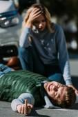 Fényképek megsérült fiatal férfi feküdt road és a találat középső ujj forgalom ütközés után