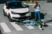 pohled z vysokého úhlu ženy stojící poblíž zraněný cyklista po dopravní nehodě
