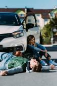 Fényképek fiatal kerékpáros feküdt road és a nő ül közelében autó gépjármű ütközés után megsérült
