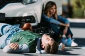 zraněný mladý cyklista ležící na silnici po kolize motorových vozidel
