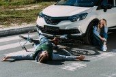 Fotografie pohled z vysokého úhlu cyklista ležící na silnici a strach žena pláče u vozu po dopravní nehodě