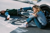 Fényképek magas, szög, kilátás a fiatal nő ül autó és úton fekvő autóbaleset áldozata