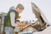 Fotografie boční pohled mladého muže, kontrola hladiny motorového oleje v rozbité auto