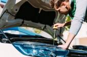 mladý muž, kontrola hladiny motorového oleje v rozbité auto