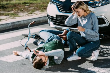 shocked young woman looking at injured cyclist lying with bicycle at car accident