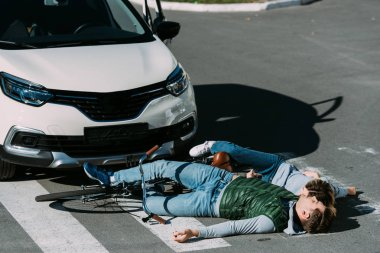 young cyclists lying on road at car accident