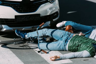 cropped shot of young cyclists lying on road after traffic collision
