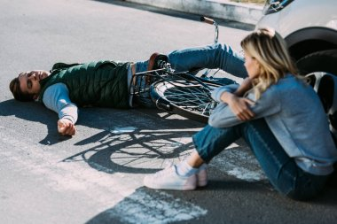 car driver sitting on road and looking at injured cyclist after car accident