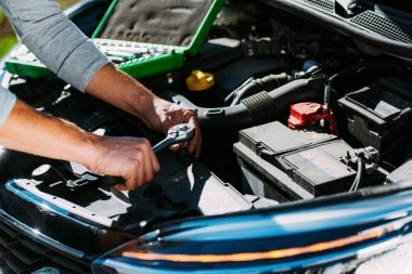 Close-up partial view of young man fixing broken car engine stock vector