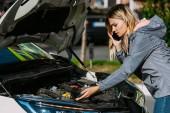 emocionální mladá žena mluví o smartphone a při pohledu na rozbité auto motor