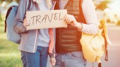 cropped shot of young couple with backpacks holding card with inscription travel