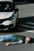 Fényképek magas, szög, kilátás a sérült fiatal férfi feküdt a közúti forgalom ütközés után