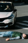 Fényképek magas, szög, kilátás a sérült fiatal férfi feküdt road autó baleset után