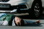 Detailní pohled zraněného mladého muže ležícího na silnici po dopravní nehodě