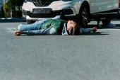 hladinou zraněného mladého muže ležícího na silnici po dopravní nehodě
