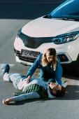 Fotografie pohled z vysokého úhlu mladé ženy při pohledu na dojemné zraněného muže ležícího na silnici po dopravní nehodě