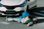 žena poslechu tep zraněného muže ležícího na silnici po dopravní nehodě