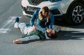 Fotografie vysoký úhel pohledu vyděšená mladá žena dotýká zraněný muž ležel na silnici po dopravní nehodě