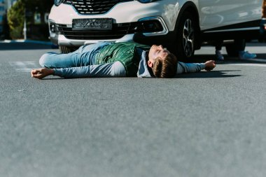 surface level of injured young man lying on road after car accident