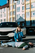 Fotografie young woman calling emergency while kneeling near injured man after traffic accident