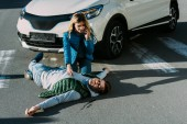Fotografie high angle view of scared young woman calling emergency and touching injured man on road after traffic accident