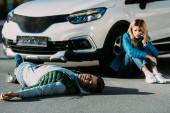 mladá žena volá nouzové zatímco poraněného muže ležící na silnici po kolize motorových vozidel