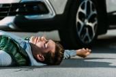 boční pohled na zraněného mladého muže ležícího na silnici po dopravní nehodě