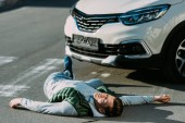 Fotografie injured young man and car on road after traffic accident