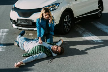 high angle view of scared young woman calling emergency and touching injured man on road after traffic accident