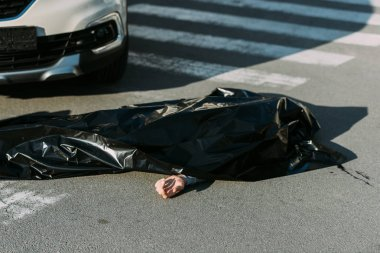 high angle view of corpse and car on road after traffic accident