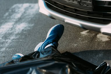 cropped shot of dead man and car on road after motor vehicle collision