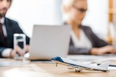 toy airplane at wooden table with office worker on blurred background