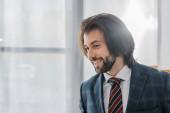 mladá usměvavá podnikatel v obleku, stojící v úřadu
