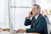 pro dospělé usmívající se podnikatel v brýlích mluví na smartphone a používat přenosný počítač v kanceláři