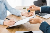 Fotografie insurance agent holding keys while woman signing contract on clipboard