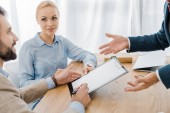 couple signing contract on clipboard with insurance agent in office