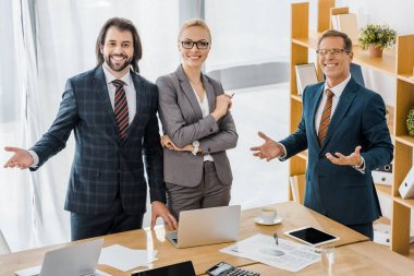 smiling insurance agents standing near table in office