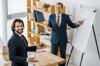 insurance workers having discussion at meeting and smiling man pointing at white board in office