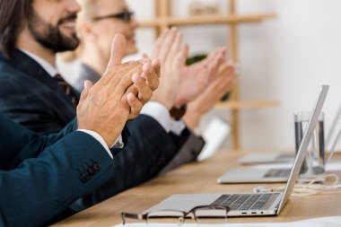 happy business people clapping hands at meeting in office